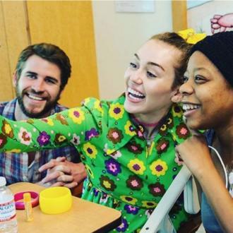Liam Hemsworth supports Miley Cyrus at children's